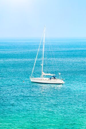 Sailboat among beautiful blue sea in sunny day, summer traveling on the water transport, luxury summertime vacation 写真素材