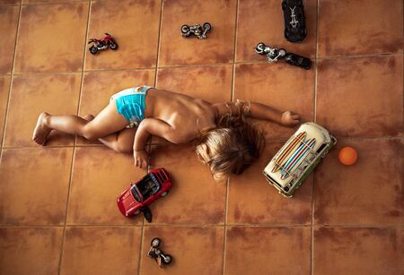 Cute little boy lying down on the floor and playing with models of cars and motorcycles at home, leisure time concept 写真素材