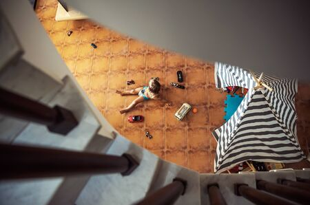 Little boy having fun at home, lying down on the floor under stairs and playing with cars models, spending summer holidays at home