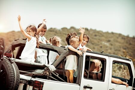 Happy kids enjoying road trip in the open-top 4x4, cheerful boys and girls having fun in the car riding along mountains, happy active summer holidays 写真素材