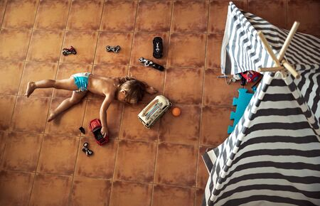Cute little boy acostado en el suelo y jugando con modelos de coches y motos en casa, concepto de tiempo libre