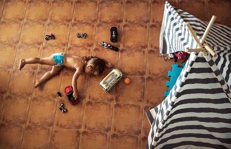 Mignon petit garçon allongé sur le sol et jouant avec des modèles de voitures et de motos à la maison, concept de loisirs