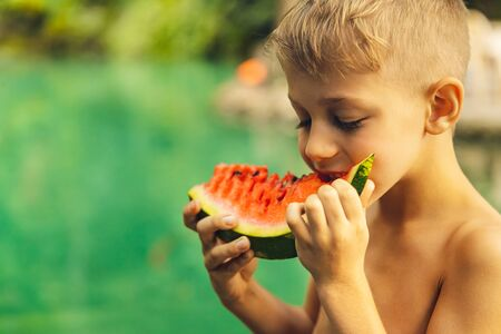 Portrait of a cute little boy with pleasure eating watermelon outdoors, enjoying fresh ripe juicy fruit, happy summer holidays