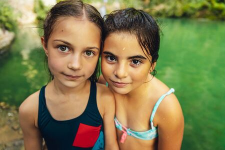 Portrait of a two cute little girls standing near the mountains lake, with pleasure spending time in summer camp, happy best friends enjoying summer time together
