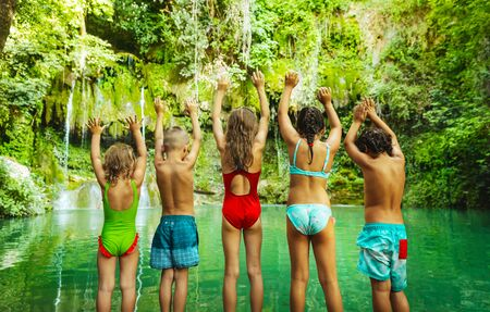 Happy children jumping into the mountains lake, amazing nature, great greenery surrounded the lake, holidays in the beautiful natural place, summer camp