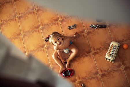 Top view from stairs on the little baby boy playing with toys, spy on the baby when he plays, spending happy time at home