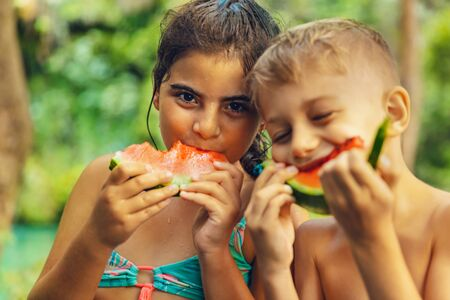 Portrait of a two happy friends eating sweet tasty watermelon outdoors, with pleasure biting fresh juicy fruit, boy and girl having picnic on the beach