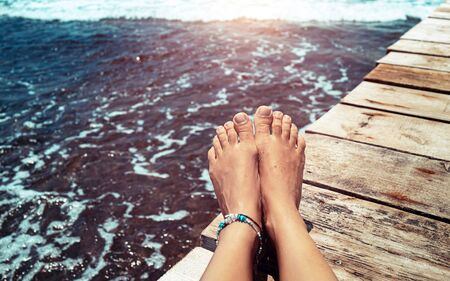 Closeup photo of a womens legs on the wooden pier over the sea, female with pleasure tanning on the beach, summer vacation concept