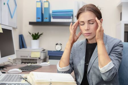 Tired woman at work, beautiful businesswoman in the office suffers of headache, problems with documents, hard office work concept 写真素材