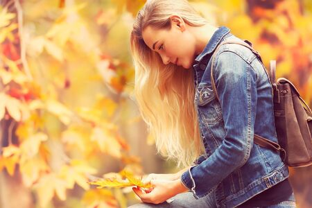 Beautiful model in autumn park, attractive female standing side view and posing over autumnal background, enjoying fall nature