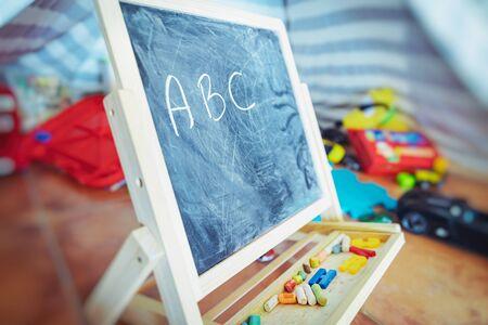 Pequeña pizarra de pie entre diferentes juguetes en la habitación de un bebé, comienza a aprender el alfabeto, educación de preescolares, concepto de regreso a la escuela