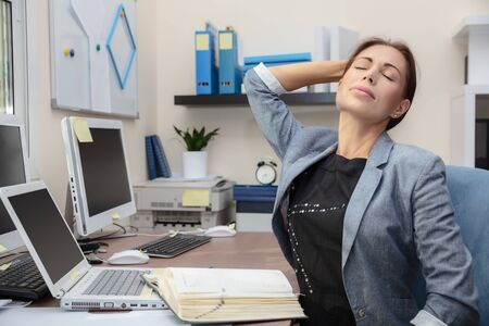 Exhausted business-woman working hard in office, deadline pressure, business life concept 写真素材