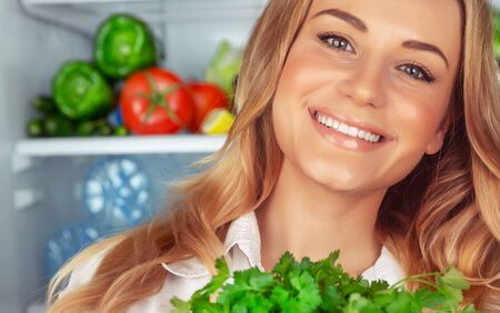 Healthy eating, closeup portrait of a beautiful girl with perfect smile standing near open refrigerator and choosing ingredient for green salad, vegetarian nutrition, weight loss, healthy lifestyle