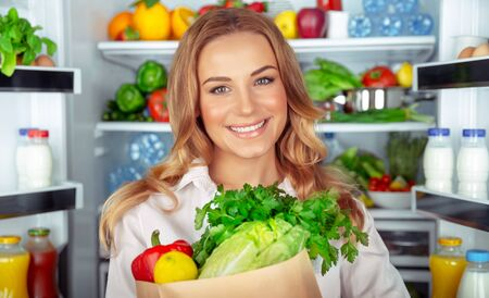 Vegetarian lifestyle, portrait of a beautiful woman standing near open fridge full of different fresh vegetables, organic nutrition, weight control, healthy eating concept