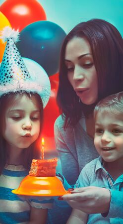 Birthday girl celebrating holiday with family, portrait of a beautiful young mother with two cute kids blow out candle on a festive cake, party decorated with colorful balloons 写真素材