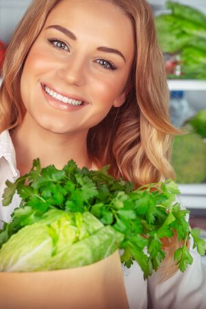 Healthy eating, portrait of a beautiful girl with perfect smile standing near open refrigerator and choosing ingredient for green salad, vegetarian nutrition, weight loss, healthy lifestyle