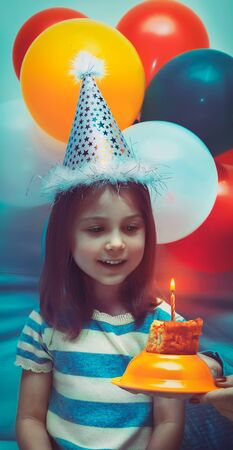 Portrait of a cute little birthday girl wearing festive hat and getting ready to blow out one candle on a birthday cake, party decorated with many colorful balloons