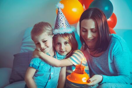 Happy family celebrating birthday, little boy with mom congratulating his sister with birthday, enjoying festive cake and many colorful balloons