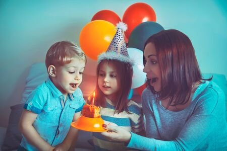 Little birthday boy celebrating holiday with family, portrait of a beautiful young mother with two cute kids blowing out candles on a festive cake, home party decorated with colorful balloons