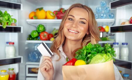 Healthy nutrition concept, portrait of a beautiful young woman standing near open refrigerator