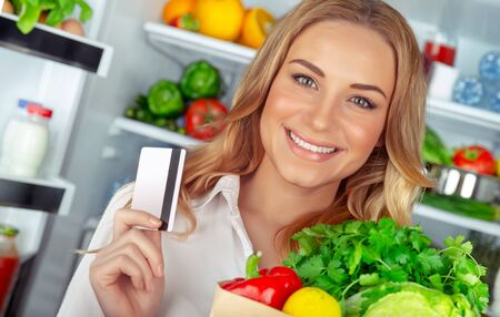 Buyer of a healthy food, portrait of a nice female with a credit card and a paper bag full of fresh vegetables 写真素材