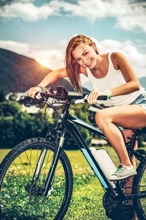 Portrait of a happy woman riding on bicycle along mountainous village in Alps