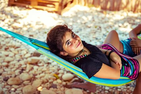 Little girl chilling out in hammock on the beach