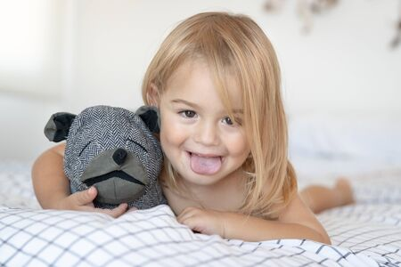 Portrait of a happy little baby boy having fun at home, lying down on the bed with favourite soft toy and making faces, enjoying childhood