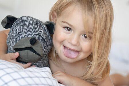 Closeup portret van een schattige babyjongen die gezichten maakt, de tong laat zien, plezier heeft thuis met zijn kleine vriend, zacht hondenspeelgoed, gelukkige gezonde zorgeloze jeugd Stockfoto