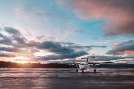 Airplane in sunset light, beautiful cloudy sky, luxury transport, travel to Norway, Scandinavia, North Europe