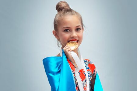 Portrait of cute little girl biting golden medal, isolated on a gray background, the winner of rhythmic gymnastics competitions, satisfaction from victory, hard work pays concept Standard-Bild