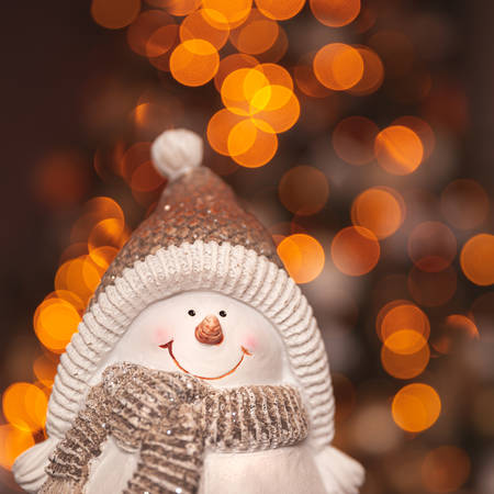 Cute little snowman decoration over blurry bokeh background, traditional wintertime symbol, Merry Christmas and happy New Year