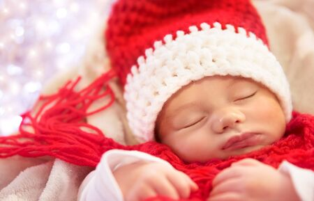 Portrait of a sweet newborn baby wearing red knitted Santa hat and scarf, sleeping at home, cute little child dreaming about magic of Christmas holidays