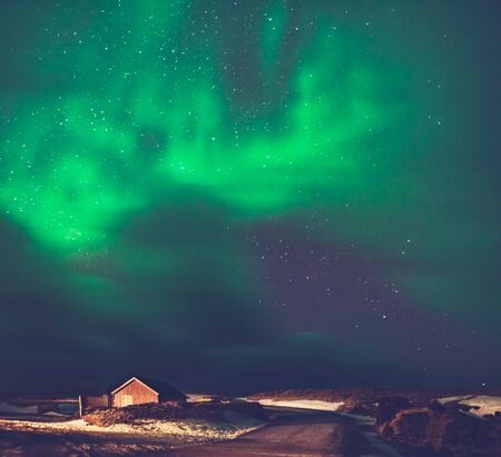 Amazing view of Aurora Borealis, magical green lights in the sky over little village in Iceland, forces of nature, Northern light Stock Photo