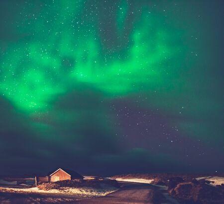 Niesamowity widok na Aurora Borealis, magiczne zielone światła na niebie nad małą wioską na Islandii, siły natury, zorzę polarną