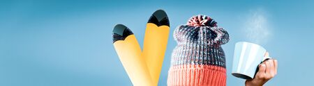 Winter vacation conceptual background, person wearing colorful knitted hat holding cup of hot drink and ski over blue clear sky background, happy sportive winter holidays Banque d'images - 140538230