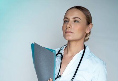 Serious concerned woman doctor with medical records in hands, isolated on gray background, thoughtfully looking away, health and medical care
