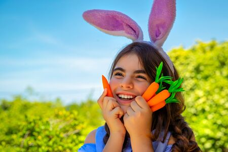 Portrait of a cute little bunny girl with carrots in hands enjoying Easter