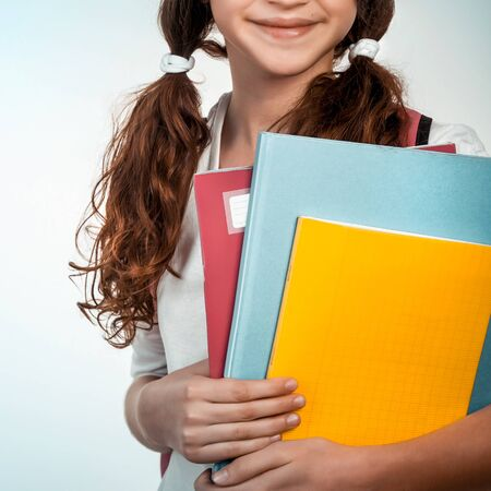 Portrait of cute brunette schoolgirl holding in hands three colorful notebooks, face part, isolated on clear background, back to school concept
