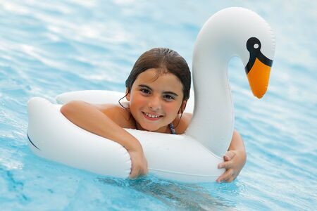 Portrait of a Cheerful Small Girl Having Fun in the Swimming Pool. Young Little Lady on the Swan. Happy Summer Day in Aqua Park.