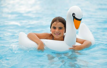 Cute Little Girl Enjoying Summer Holidays on the Beach Resort. Sweet Baby Swimming in the Pool in the Rubber Ring in Swan Shape. Happy Summer Activity.