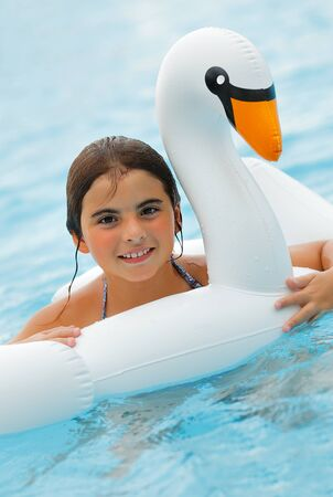 Portrait of a Cheerful Little Girl Having Fun in the Swimming Pool. Young Pretty Lady with Pleasure Floating on the Rubber Ring in Swan Shape. Happy Summer Day in the Aqua park.