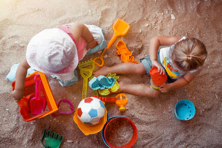 Two Happy Little Kids Playing with Different Colorful Sand Toys. With Fun and Joy Spending Holidays on the Beach Resort. Active Summer Games. Sandbox Playground. Flat Lay.