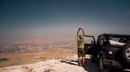 Tourist on the Break from a Long Ride. Standing near the Car and Stretching. Enjoying Amazing View of Bekaa Valley. Active Summer Vacation. Road Trip. Freedom Concept. Lebanon
