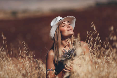 Portrait of a Happy Young Blond Woman Outdoors. Girl Holding Lavender Flowers Bouquet. Standing in a Wheat Field. Enjoying Nature. Beautiful Sunny Day. Banque d'images