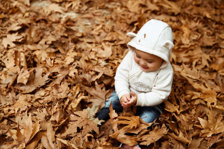 Cute little baby boy sitting on the graund in the forest and with pleasure playing with dry tree leaves, enjoying autumn nature