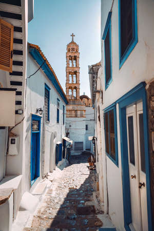 Beautiful Narrow Streets in Greece. An Old High Chapel Can be Seen in the Distance. Traditional White Facades Of Houses. Beauty and Coziness of a Little Greek Town. Banque d'images