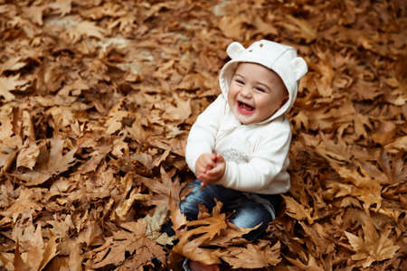 Cute little boy sitting in the pile of dry tree leaves and laughing, enjoying beauty and warm weather of autumn season