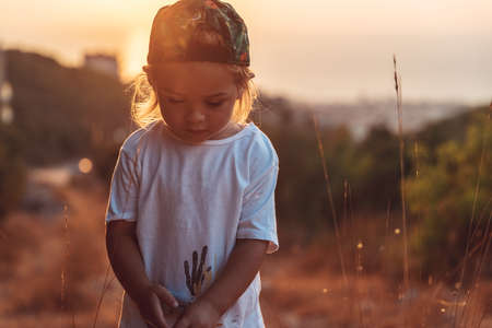 Cute little boy on the walk, sweet child with pleasure spending time outdoors, enjoying warm summer evening and beautiful sunset