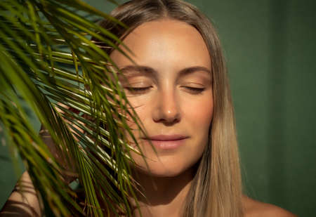 Portrait of a Beautiful Young Woman with Closed Eyes. Nice Female on the Beach. Authentic Women's beauty. Natural makeup. Perfect Skin Tan.